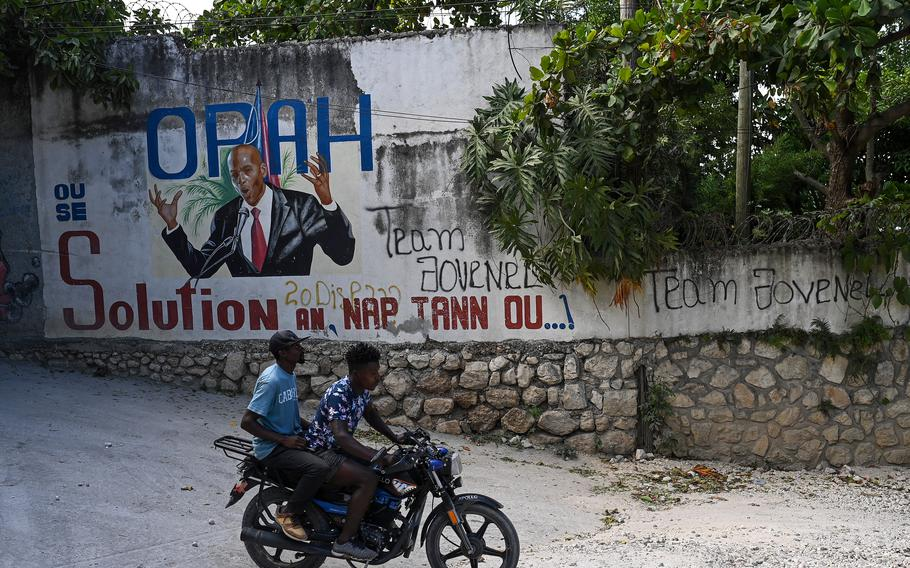 Motorcyclists ride past a mural in Port-au-Prince of the late Haitian President Jovenel Moïse the day before he was laid to rest.
