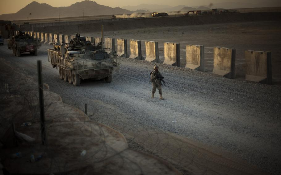 U.S. soldiers from the 5th Striker Brigades walk next to armored vehicles as they arrive at their base on the outskirts of Spin Boldak, about 63 miles southeast of Kandahar, Afghanistan, Aug. 8, 2009.
