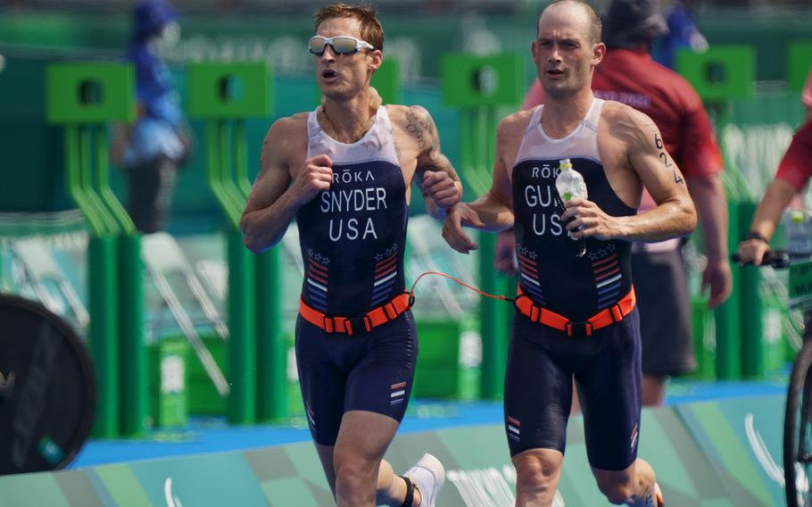 Team USA's Bradley Snyder, left, and Greg Billington run in a Tokyo Paralympics triathlon at Odaiba Marine Park, Saturday, Aug. 28, 2021. Snyder is a Navy veteran who lost his sight from a blast in Afghanistan in 2011.