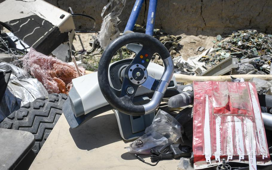 Workers at a trash yard outside Bagram Airfield, Afghanistan, displayed an Xbox controller for driving games on a special table June 5, 2021. A surge of containers and junk have been trucked out of Bagram since May, residents near the base said.