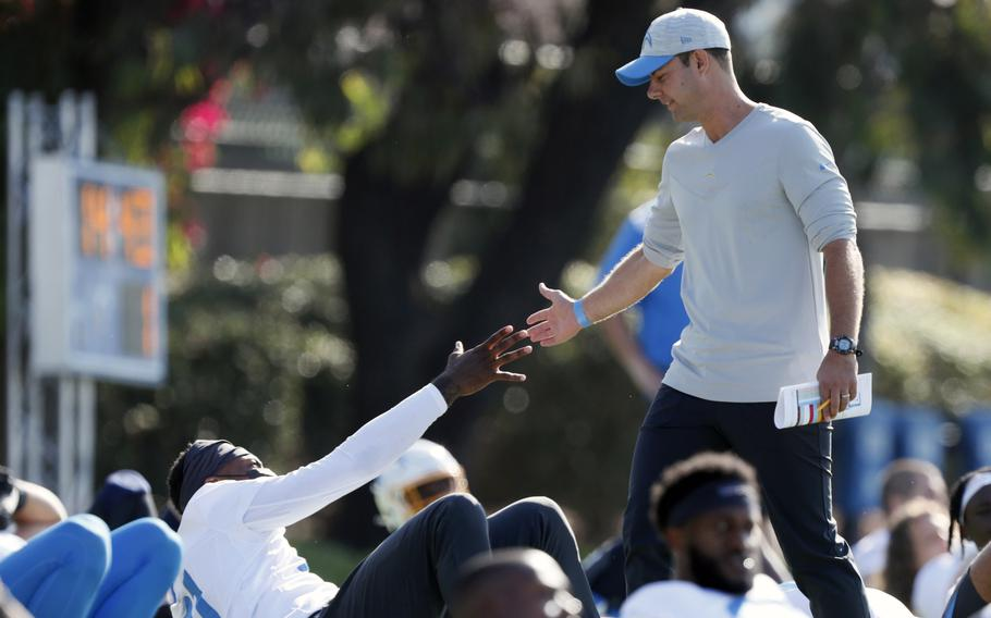 Los Angeles Chargers head coach Brandon Staley greets wide receiver Mike Williams during practice at the NFL football team's training camp July 28 in Costa Mesa, Calif. As workers return to the office, friends reunite and more church services shift from Zoom to in person, this exact question is befuddling growing numbers of people: to shake or not to shake.