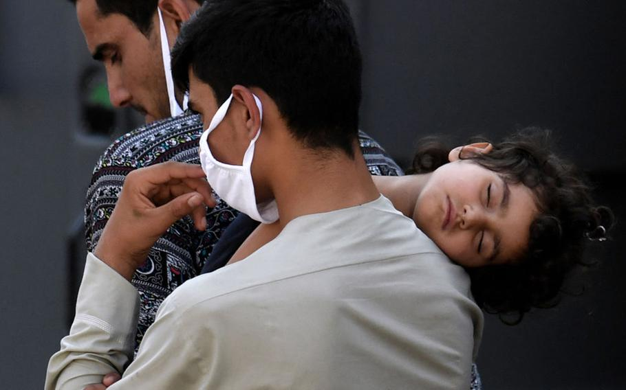 Afghan refugees arrive at a processing center in Chantilly, Va., on Aug. 23, 2021, after arriving on a flight at Dulles International Airport.