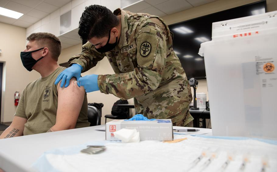 Army Cpl. Jonathan Leon Camacho, a practical nursing specialist with Dwight D. Eisenhower Army Medical Center at Fort Gordon, Ga., injects an Army Reserve soldier from the 447th Military Police Company with the coronavirus vaccination, Aug. 21, 2021, at Camp Shelby Joint Forces Training Center, Miss.