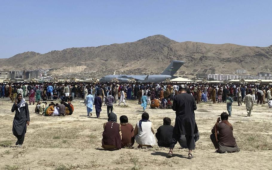 In this Aug. 16, 2021, file photo hundreds of people gather near a U.S. Air Force C-17 transport plane along the perimeter at the international airport in Kabul, Afghanistan.