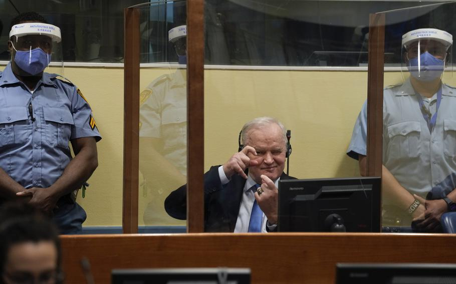 Former Bosnian Serb military chief Ratko Mladic imitates taking pictures as he sits in the court room in The Hague, Netherlands, Tuesday, June 8, 2021, where the United Nations court delivers its verdict in the appeal of Mladic against his convictions for genocide and other crimes and his life sentence for masterminding atrocities throughout the Bosnian war.