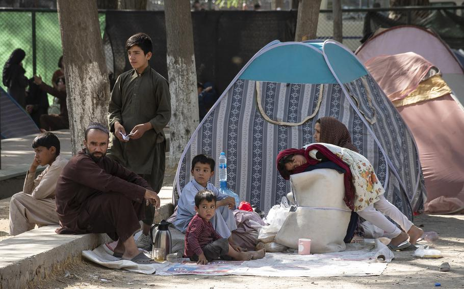 A family waits at a Kabul park on Friday, Aug. 13, 2021. Thousands of Afghans have fled to the Afghan capital after the Taliban began overtaking cities across the county during the past week.