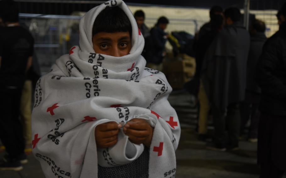 An Afghan boy keeps warm inside a Red Cross blanket during a recent chilly night inside the temporary living facilities for evacuees from Afghanistan at Ramstein Air Base, Germany, Sept. 2, 2021.