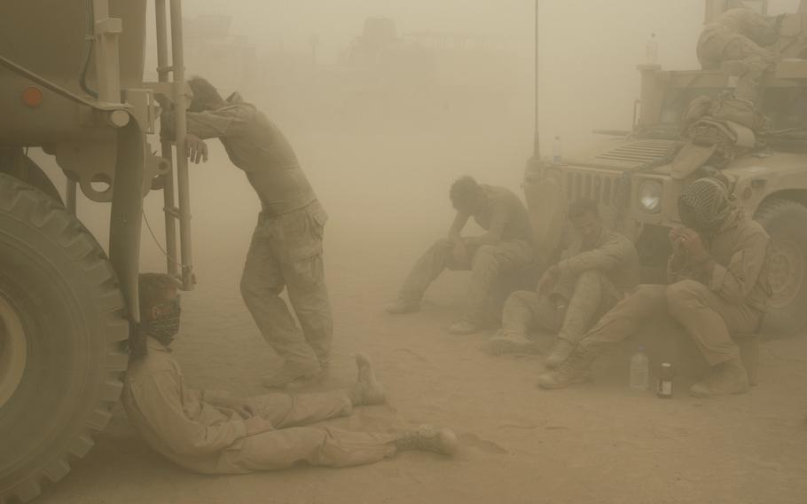 U.S. Marines from the 24th Marine Expeditionary Unit try to take shelter from a sand storm at forward operating base Dwyer in the Helmand province of southern Afghanistan, on May 7, 2008.