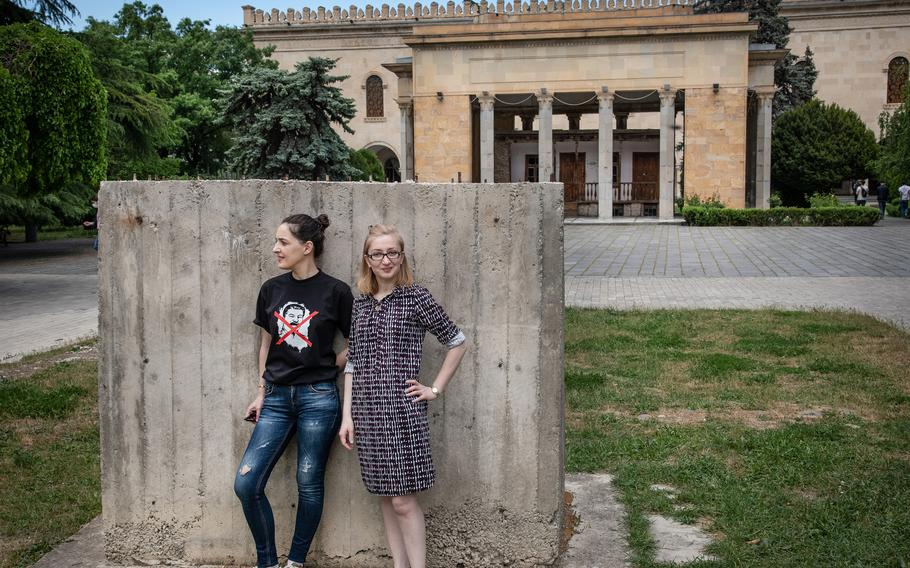 Teona Pankvelashvili, wearing a T-shirt with Stalin's face crossed out, and Nino Dalakishvili pose in front of empty pedestal outside the Stalin Museum in Gori, Georgia, on May 18, 2021. They are part of a group of local activists that prevented the restoration of the statue.