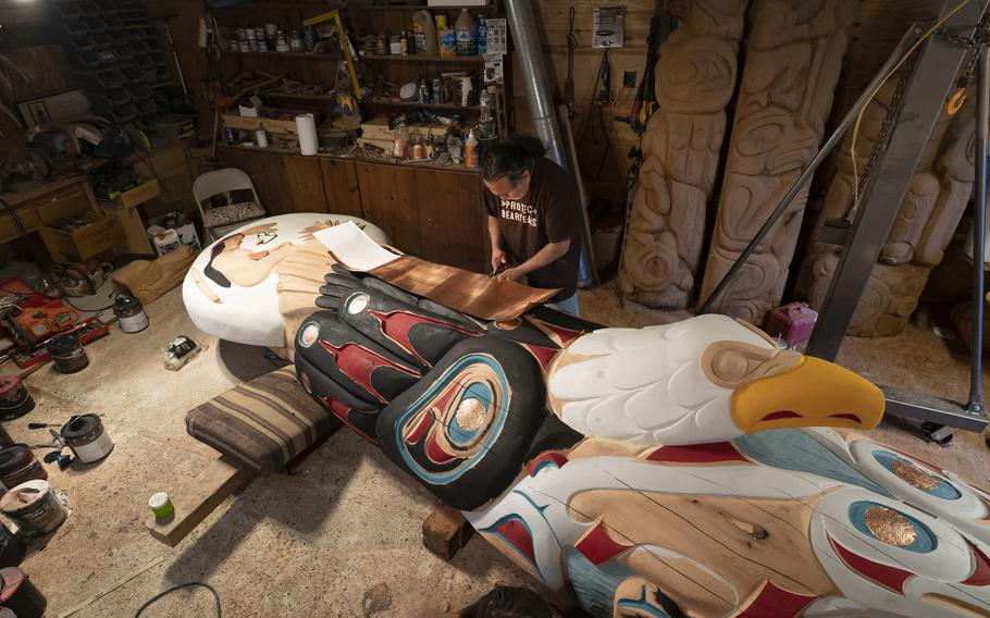"""Jewell James of the Lummi Nation works on a 25-foot totem pole he helped make as head carver for the """"House of Tears"""" carvers. The pole is making a cross-country trip with a crew of travelers in July from Washington state to Washington D.C. to raise awareness about Native American issues and sacred sites."""