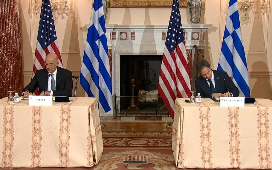 In a screenshot from Twitter, Secretary of State Antony Blinken, right, and his Greek counterpart Nikos Dendias sign the renewal of the U.S.-Greece Mutual Defense Cooperation Agreement after talks in Washington, Oct. 14, 2021.