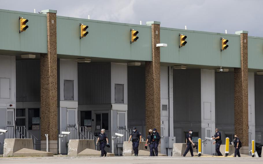 Border guards walk to their booths at the Ambassador Bridge in Windsor, Ontario, Canada, on May 26, 2021.