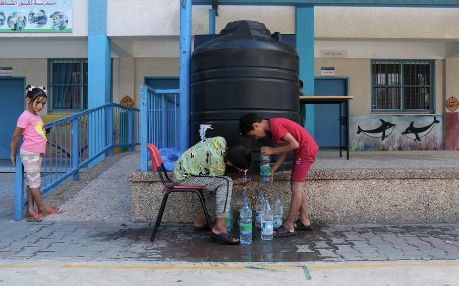 Ahmed Hassanian, left, and his brother Moataz are filling water bottles.