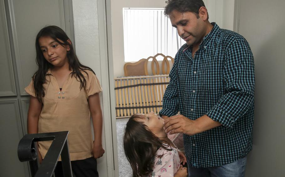 Sayed Omer Sadat, 35, an Afghan refugee, with his two daughters Asma, 11, left, and Aqsa, 6, is seen in his new apartment in El Cajon, Calif., on Monday, Aug. 23, 2021.