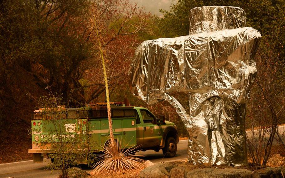 A U.S. Forest Service vehicle drives past the Sequoia National Park historic park entrance sign wrapped in fire resistant foil along Generals Highway during a media tour of the KNP Complex fire in the Sequoia National Park near Three Rivers, Calif., on Sept. 18, 2021.