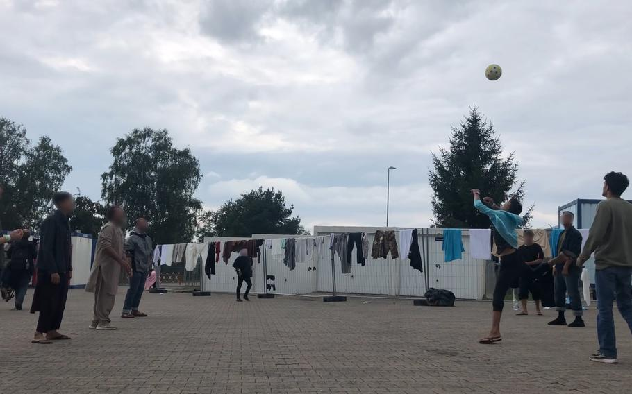 Afghan men play volleyball without a net in a concrete courtyard at Rhine Ordnance Barracks in Kaiserslautern, Germany, Aug. 30, 2021. The Army installation is housing more than 3,000 Afghan evacuees before they are resettled in the U.S.