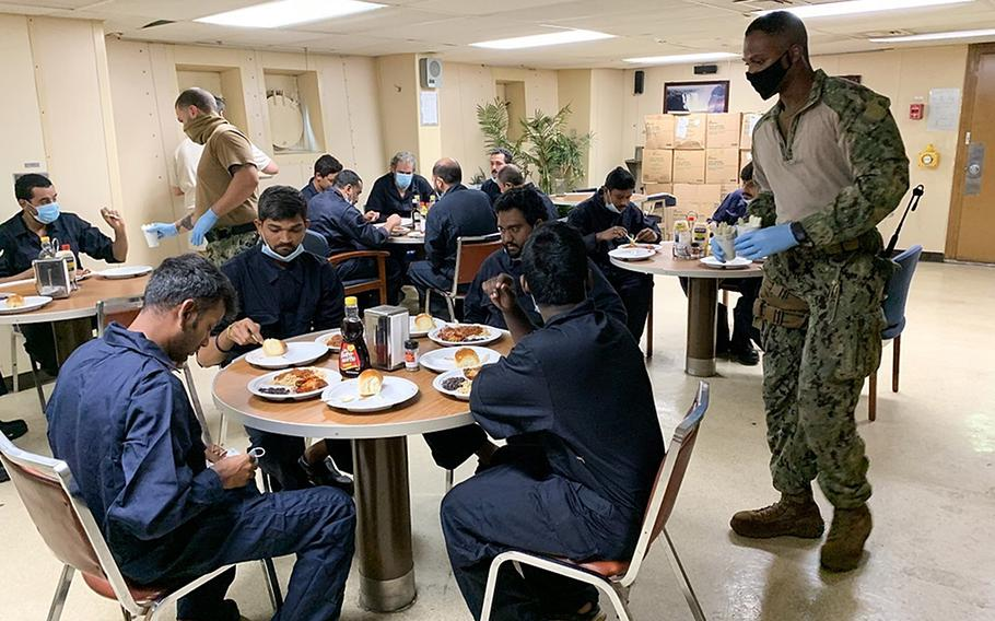 Petty Officer 1st Class Magezi Johnson and Petty Officer 3rd Class Gurney White, aboard the Military Sealift Command fleet replenishment oiler USNS Patuxent, serve hot meals to rescued crew members from the commercial ship Falcon Line, while underway in the Gulf of Aden, June 8, 2021.