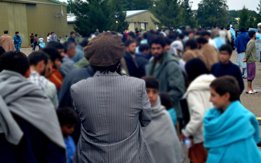 A man wearing the traditional pakol hat of northern Afghanistan waits with hundreds of other evacuees for dinner at Rhine Ordnance Barracks in Kaiserslautern, Germany, Aug. 30, 2021. The Army installation is providing food and shelter for thousands of Afghans who are transiting through Germany, most of whom will eventually be resettled in the U.S.