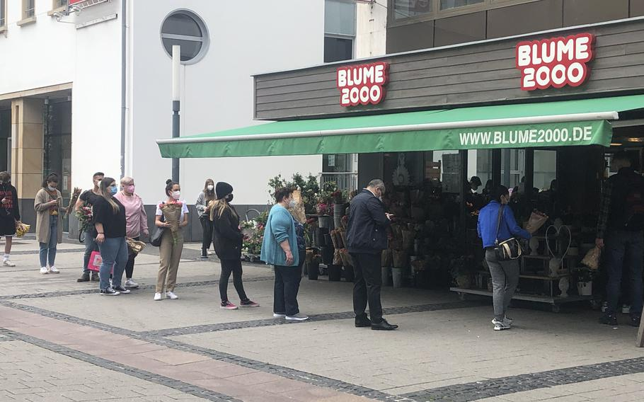 A line forms outside a flower shop in Kaiserslautern in May 2021, when strict coronavirus restrictions were in place. Many restrictions were lifted in the city and district as infections fell, but German officials reimposed some measures on July 25 as the caseload rose again.