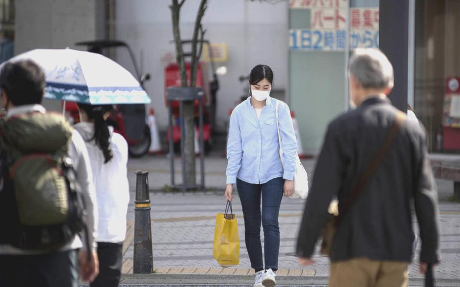 Pedestrians wear masks to guard against the coronavirus earlier this month in Zushi, Japan.