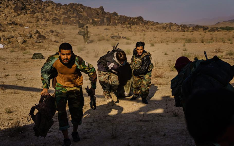 Soldiers dragging a sleeping bag with their belongings run toward a waiting UH-60 Blackhawk under fire from the Taliban in the Shah Wali Kot district of Kandahar, Afghanistan.