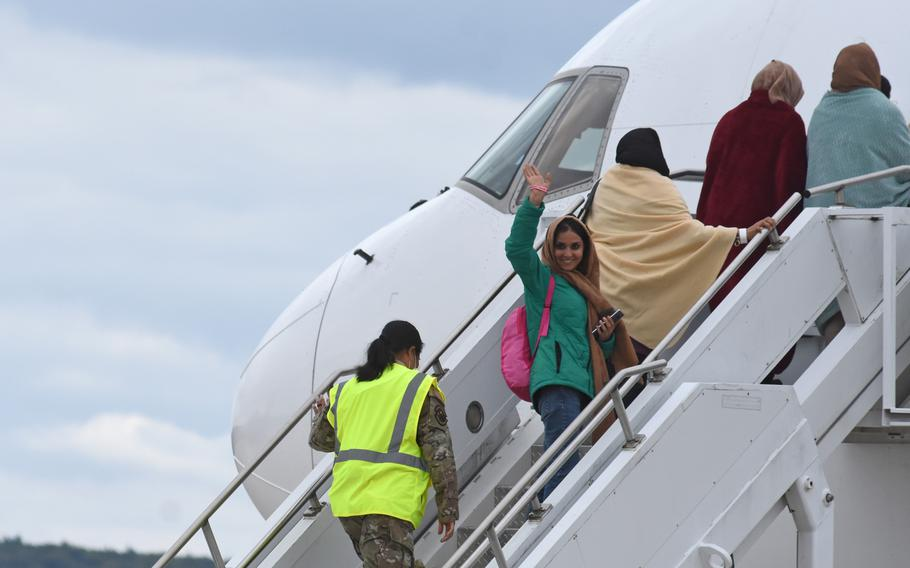 A woman waves before boarding a commercial flight taking evacuees from Afghanistan to the United States. The Boeing 767 departed Ramstein Air Base, Germany, on Aug. 26, 2021, for Dulles International Airport near Washington, D.C.