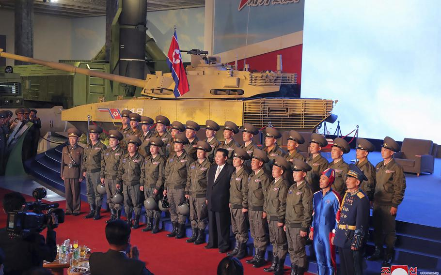 North Korean leader Kim Jong Un, center, poses for a group photo with fighter pilots who made the demonstration flight at the opening of an exhibition of weapons systems in Pyongyang, North Korea, Monday, Oct. 11, 2021.
