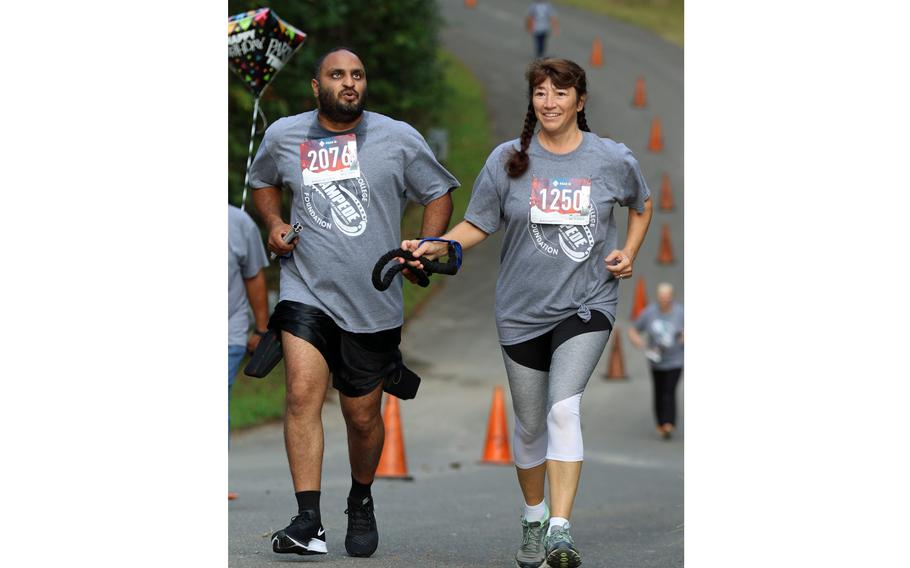 Gaston College Officer Crystal Todd helps lead blind Gaston College Alum, Angus Kola, during the inaugural Stampede for Student Success 5K Run held Oct. 2, 2021, on the campus of Gaston College in Dallas, N.C.