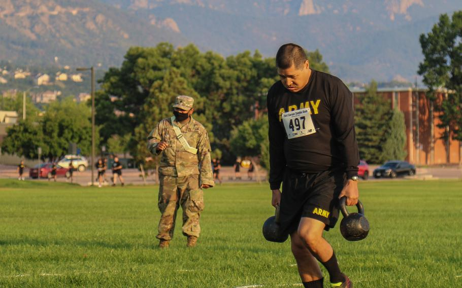 Chief Warrant Officer 3 Justin Montes, of the 4th Infantry Division, carries kettlebells during the sprint-drag-carry event of the Army Combat Fitness Test on July 21, 2021, at Fort Carson, Colo. Sgt. Maj. of the Army Michael Grinston didn't have to change his biographical blurb on Twitter, in line with a pledge he made, when soldiers couldn't register 500,000 ACFT scores by the Army's 246th birthday.