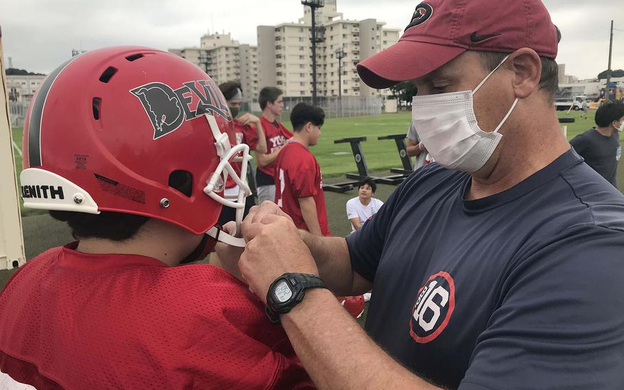 Nile C. Kinnick assistant coach Gary Wilson tends to the chinstrap on the helmet of Red Devils junior lineman Taiga Martin.