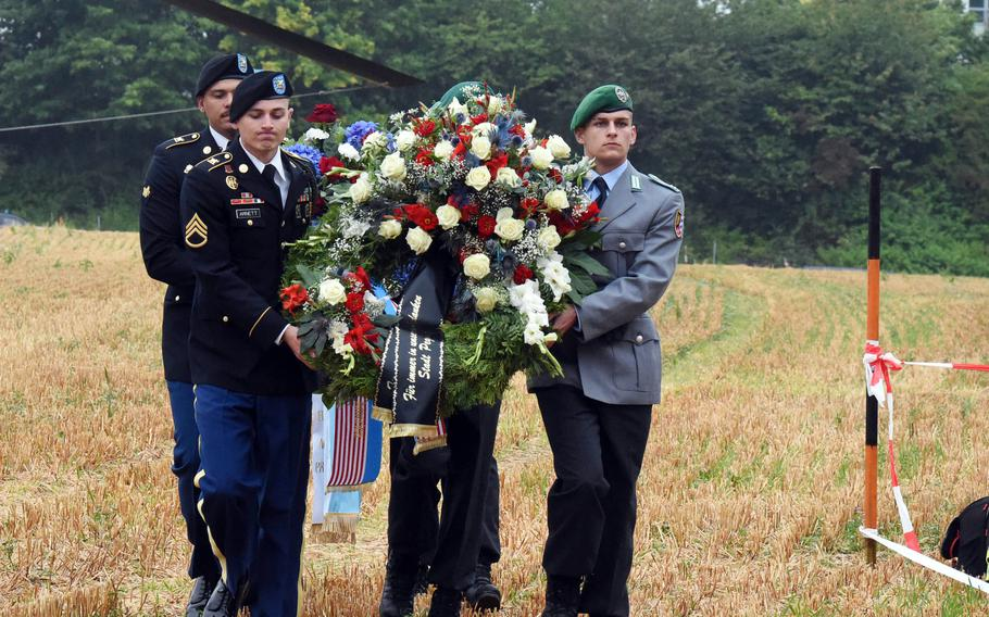 U.S. and German soldiers carry wreaths Aug. 18, 2021, from a CH-47 Chinook helicopter to the memorial site for soldiers killed in a Chinook crash 50 years ago, near Pegnitz, Germany.