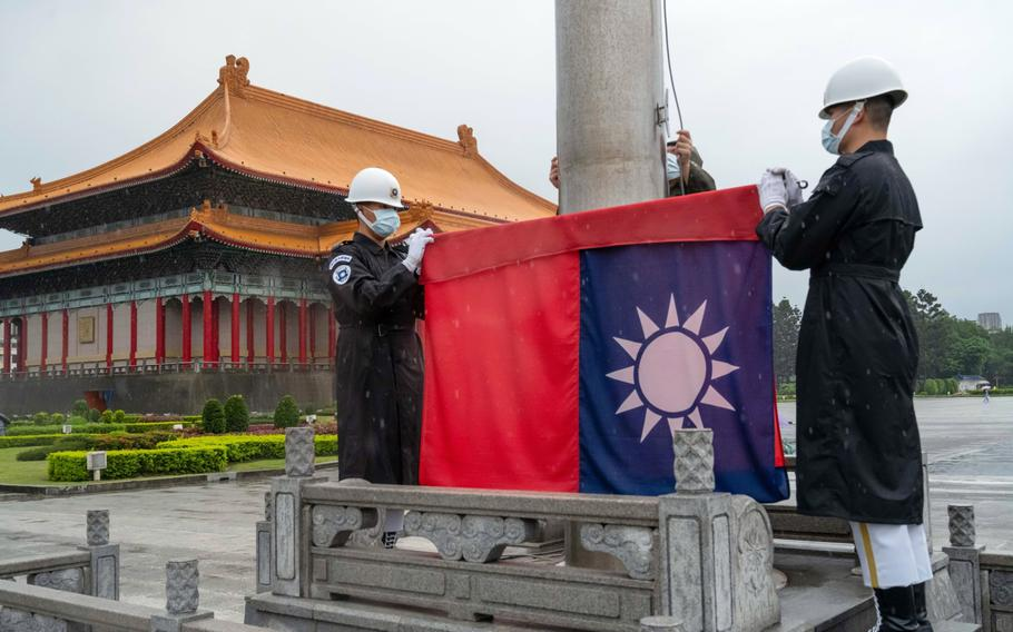 Honor guards wearing protective masks raise a Taiwanese flag at the National Chiang Kai-shek Memorial Hall in Taipei, Taiwan.