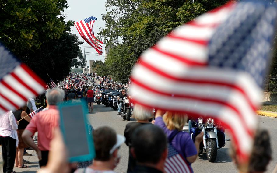 """Thousands of people on motorcycles drive past the crowd during the funeral procession for Marine Corps Cpl. Humberto """"Bert"""" Sanchez on East Market Street on Sept. 12, 2021, in Logansport, Ind."""