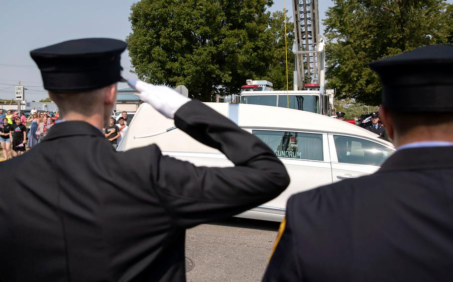 """A hearse carrying the body of Marine Corps Cpl. Humberto """"Bert"""" Sanchez passes during his funeral procession at the corner of 8th Street and East Market Street on Sept. 12, 2021, in Logansport, Ind."""