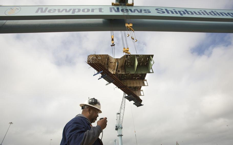 The final primary hull structure, the forward end of one of the ship's catapults, is lifted by Big Blue, the gantry crane at Newport News Shipbuilding, to the aircraft carrier Gerald R. Ford under construction in Newport News on May 7, 2013.