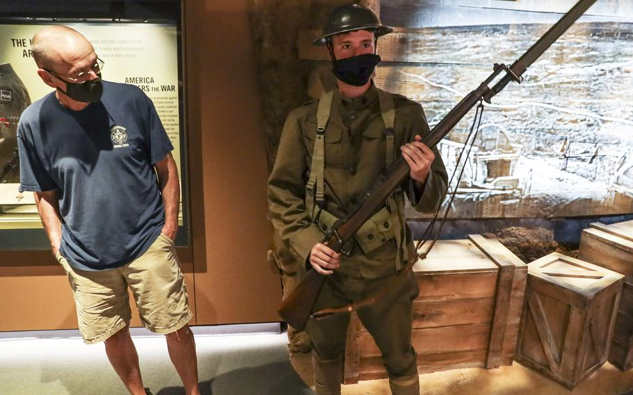 A soldier with a World War I uniform and weapon talks with visitors to the National Museum of the United States Army on its reopening day, June 14, 2021.