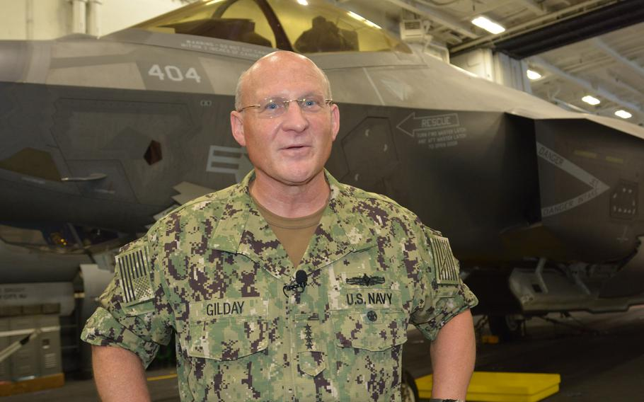 Adm. Michael Gilday, chief of naval operations, talks with reporters in the hangar deck of the USS Carl Vinson on Aug. 14, 2021.