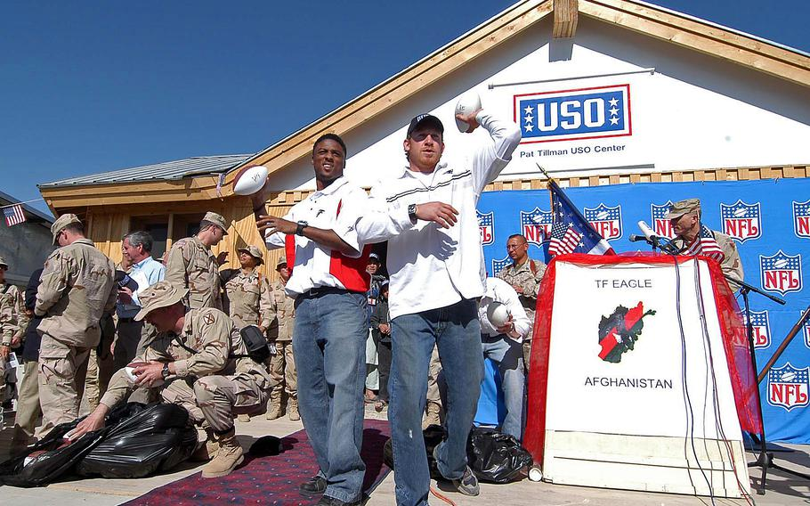 Atlanta Falcon Warrick Dunn, left, and New England Patriot Larry Izzo toss out autographed footballs to the troops before the ribbon-cutting ceremony to open the Pat Tillman USO Center on Bagram Airfield, in April 2005. The center is dedicated to the former NFL player killed in action while serving in Afghanistan in 2004.