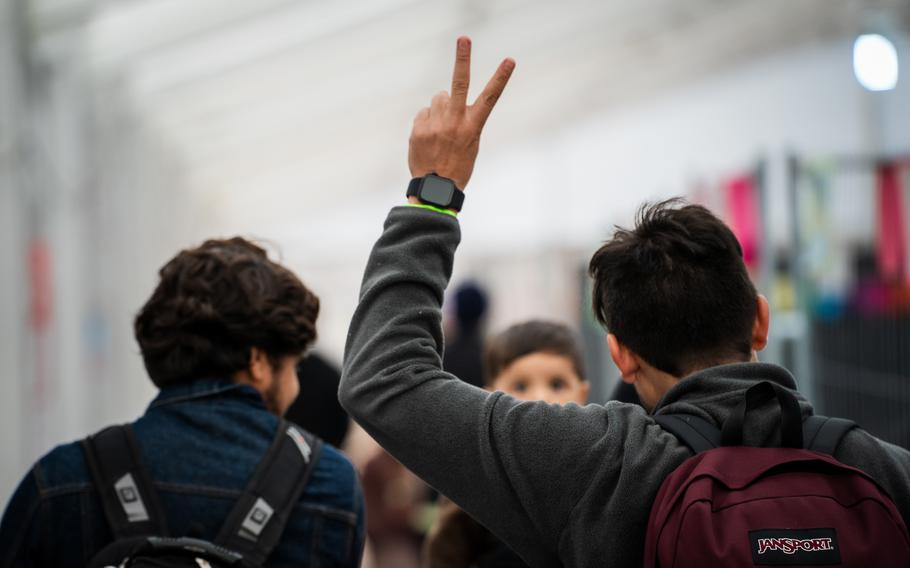 An Afghan evacuee makes a peace or victory sign as he makes his way to a waiting area in a passenger terminal at Ramstein Air Base, Germany, before traveling to the United States, Saturday, Oct. 9, 2021. Around 300 Afghans left Ramstein that day when flights for evacuees to the U.S. resumed after a three-week pause.