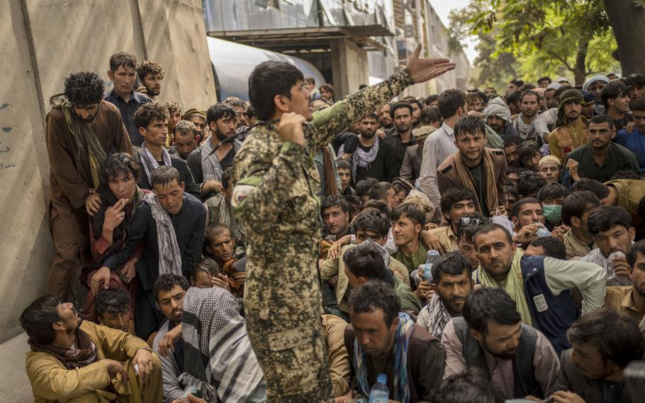Afghans wait in front of a bank as they try to withdraw money in Kabul, Afghanistan, Sunday, Sept. 12, 2021.