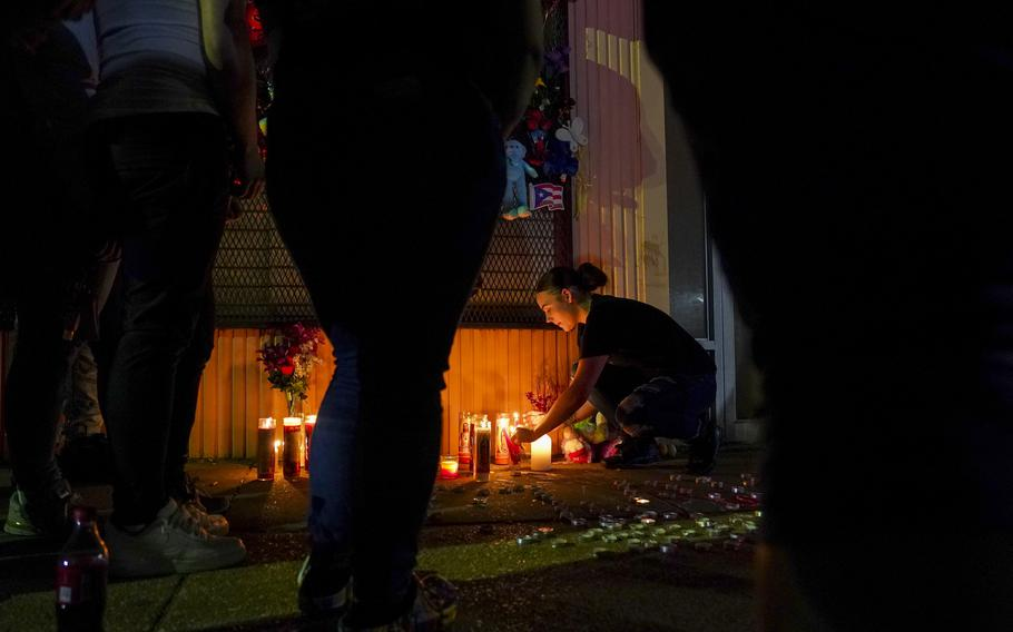 Autumn Piper lights candles during a vigil honoring Marcus Wilson, one of two men who were recently killed in the Highland town neighborhood of Baltimore in April.