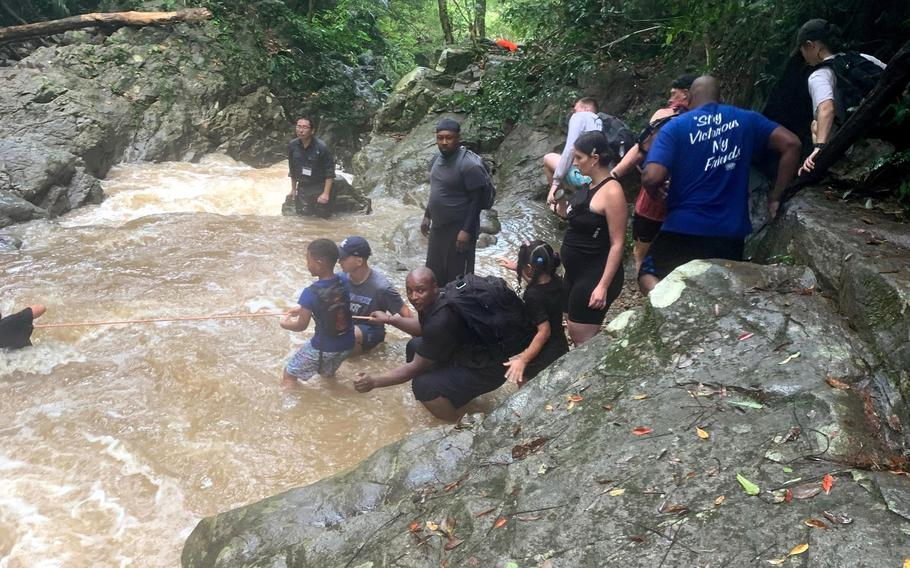 U.S. service members and their families help one another across a raging river during a flash flood at Ta-Taki Falls, Okinawa, Sept. 13, 2020.