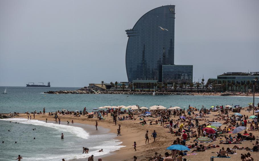 Vistors sunbathe on Barceloneta beach near the The W Hotel, operated by Marriott International Inc., in Barcelona, Spain, on June 5, 2021.