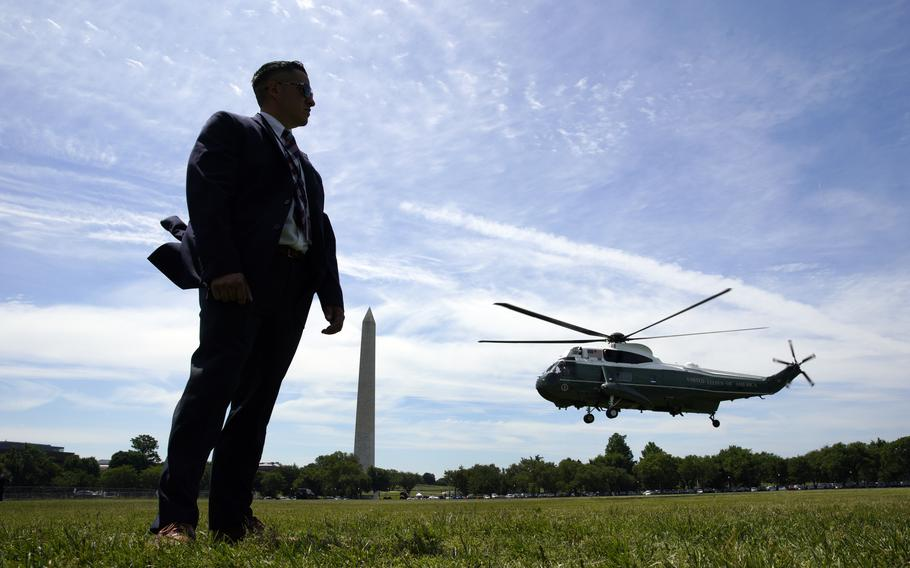 U.S. Secret Service stands guard as the Marine One helicopter, with President Joe Biden on board.