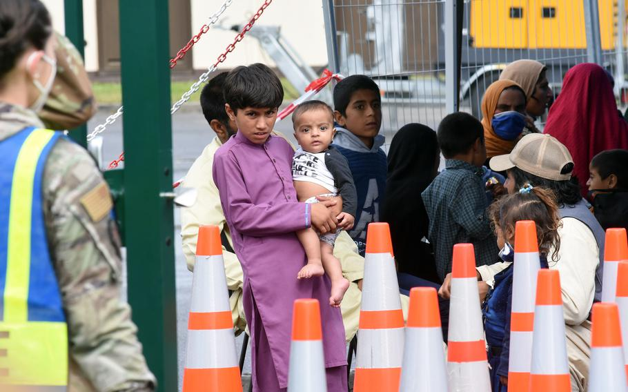A boy holds a baby while waiting for transit to temporary living facilities with other Afghan evacuees at Ramstein Air Base, Germany, Aug. 23, 2021.