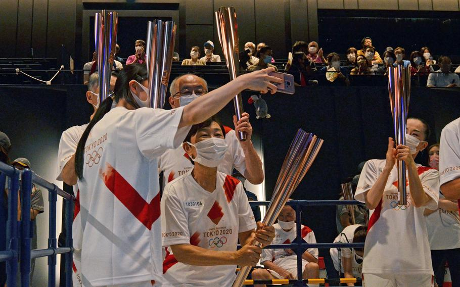 Tokyo Olympics torch relay runners take a selfie during an indoor ceremony in Tachikawa, Japan, Monday, July 12, 2021.