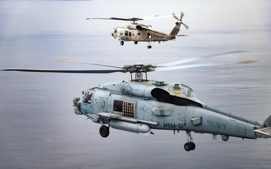 A U.S. Navy MH-60R Seahawk flies off Japan's southern coast with a Japanese Maritime Self-Defense Force SH-60K on Sept. 14, 2021.