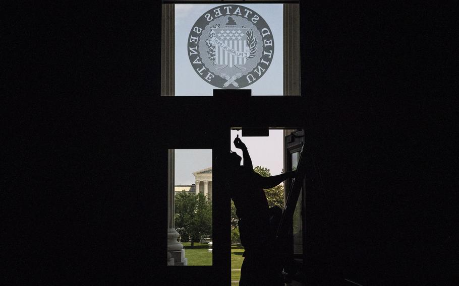A worker fixes a door at the Capitol in May 2021.