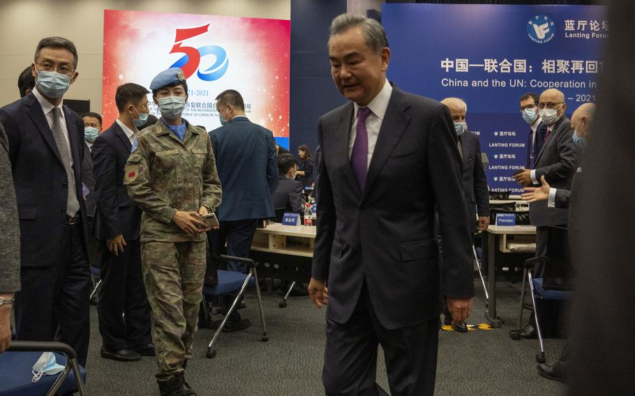 A Chinese United Nations peacekeeper looks on as Chinese Foreign Minister Wang Yi leaves after speaking at a symposium to mark the 50th anniversary of the People's Republic of China's entry into the U.N. at the Foreign Ministry in Beijing on Friday, June 25, 2021.