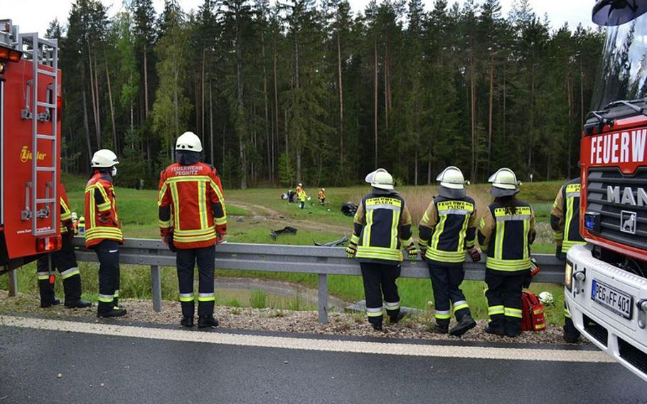 Local firefighters look at the wreckage of a car in a field near Bayreuth, Germany, May 15, 2021. A 23-year-old U.S. service member was seriously injured in the accident on the A9 autobahn.